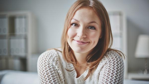 Foto van een vrouw met een tevreden glimlach.