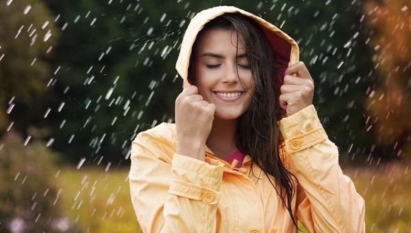 Foto van een vrouw die met haar rug naar het slechte weer gedraaid is en die zich blij voelt