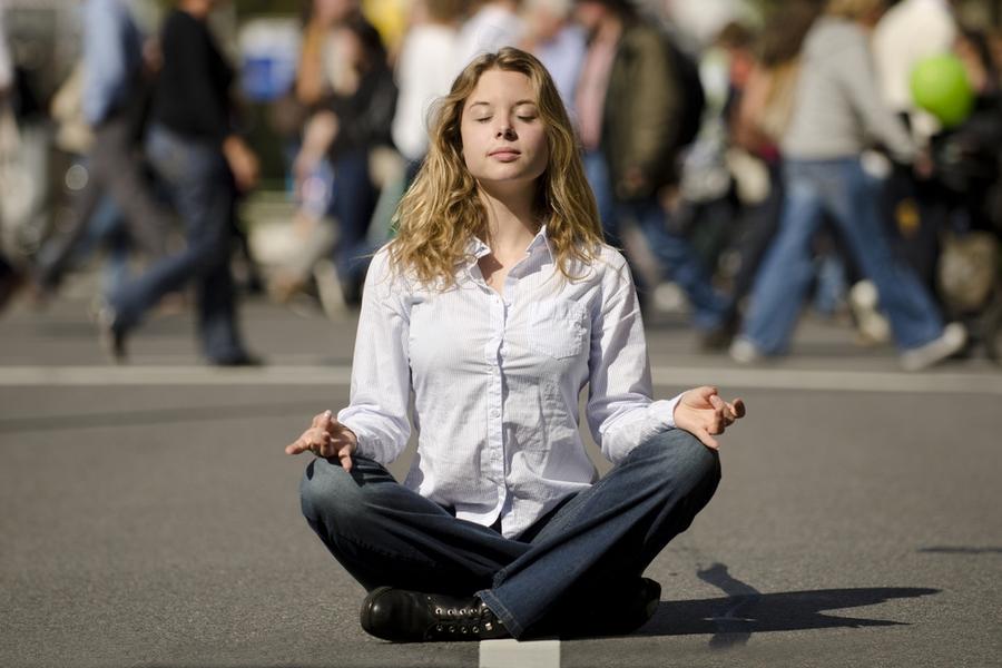 Foto van een vrouw in yogapose temidden van druk voetgangersverkeer